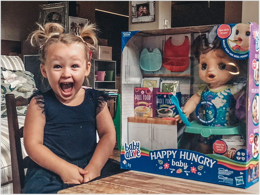 happy toddler girl with her baby alive doll