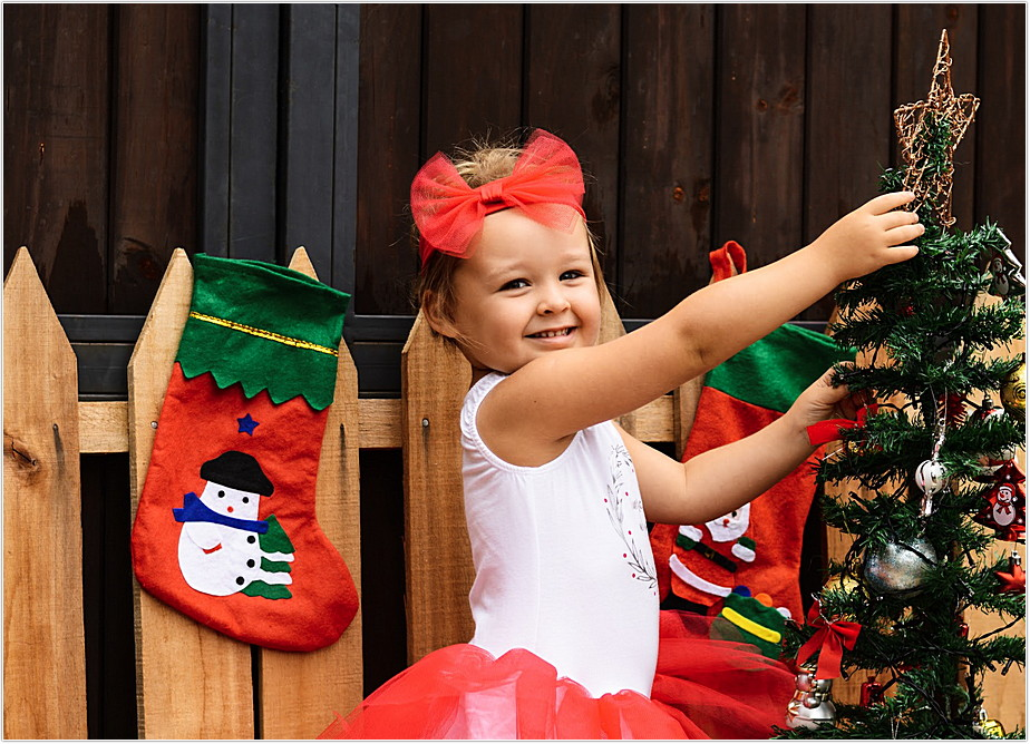 toddler girl dressed in red and white Keedo dress decorating christmas tree