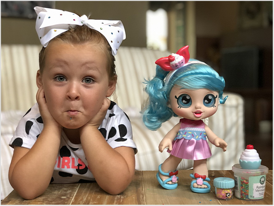 little girl next to kindi doll pulling faces