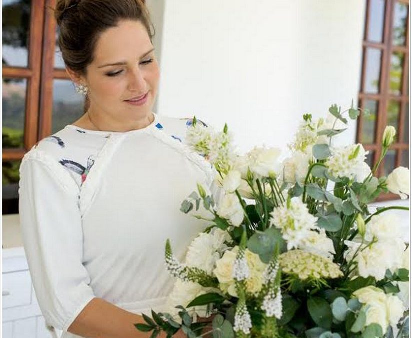 artist libby bell standing behind white flowers looking down and smiling