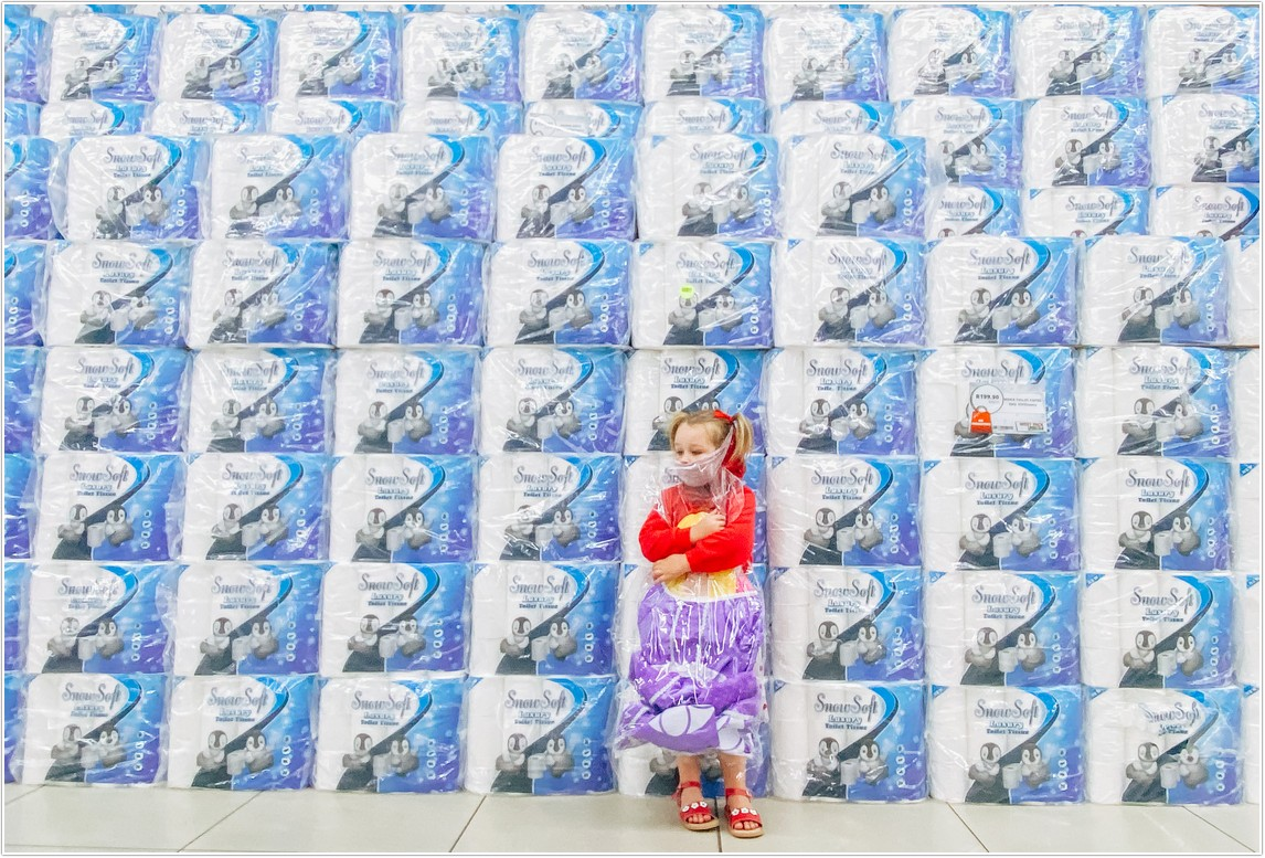 little girl standing in front of bales and bales of toilet paper clutching her paper doll in west pack lifestyle store